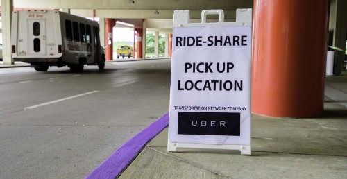 Temporary sign at PIT Airport marks where Uber pick-ups are allowed.